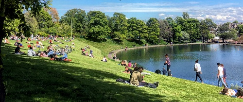 Stockbridge People Enjoying Sunny Day On Grass With Lake