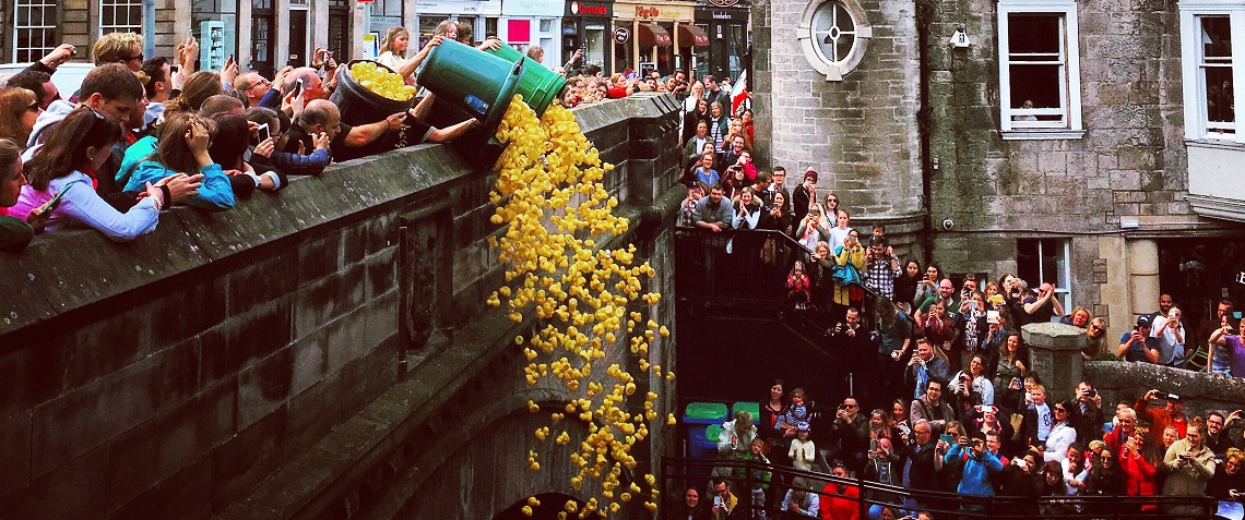 Duck Race People Throwing Toy Yellow Ducks Off Bridge Into Water To Race